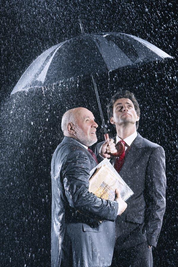 Homens de negócios que olham a chuva de debaixo do guarda-chuva fotografia de stock
