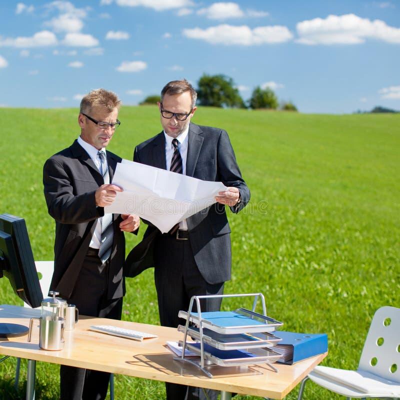 Homens de negócios que planeiam algo na natureza fotos de stock
