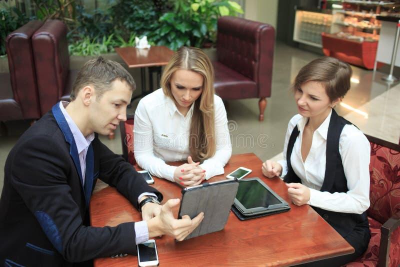 Homens de negócios que sentam-se no café para um portátil Duas meninas imagem de stock royalty free