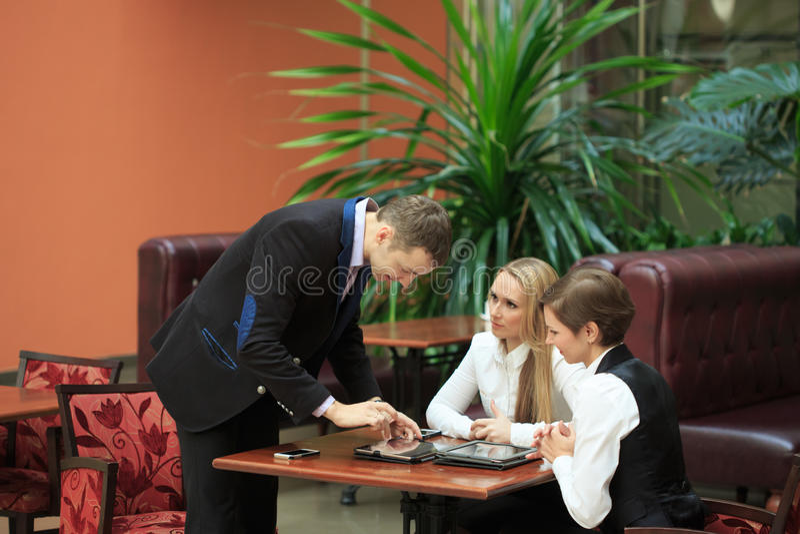 Homens de negócios que sentam-se no café para um portátil Duas meninas foto de stock royalty free
