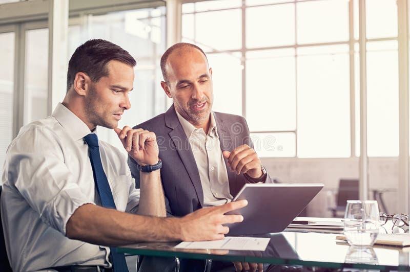 Homens de negócios que trabalham na tabuleta digital imagem de stock royalty free