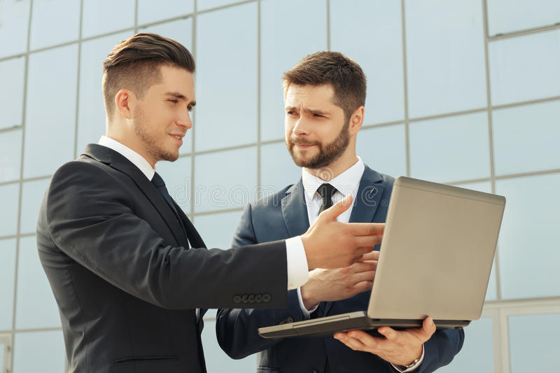 Homens de negócios que usam o portátil ao ter uma reunião imagens de stock royalty free