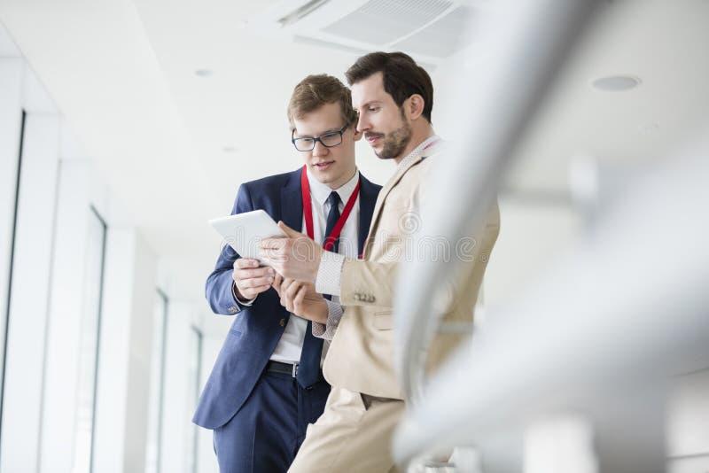 Homens de negócios que usam a tabuleta digital no centro de convenções foto de stock royalty free
