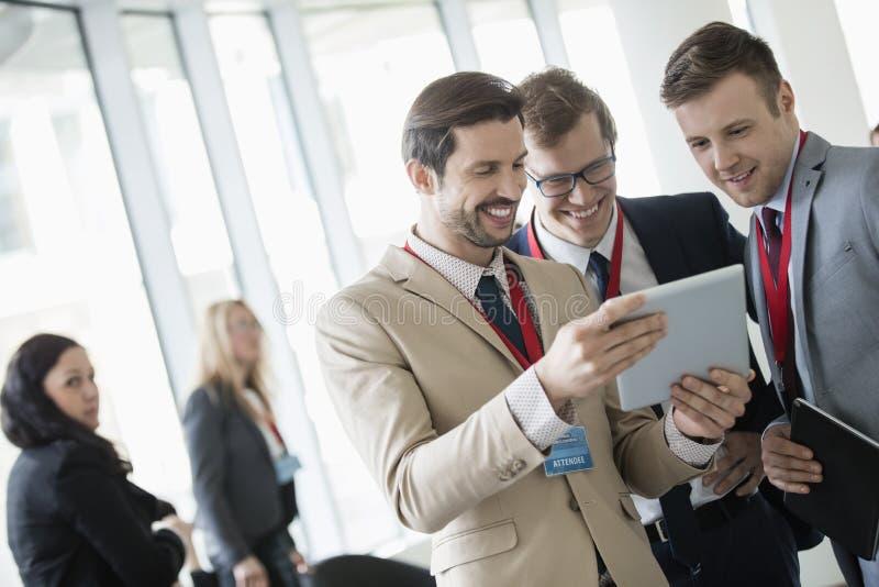 Homens de negócios que usam a tabuleta digital no centro de convenções foto de stock