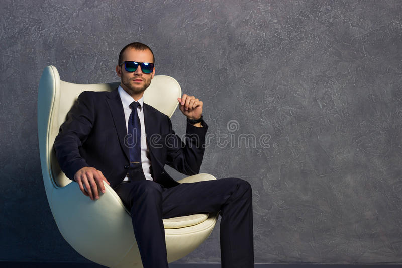 Homens de negócios 'sexy' brutais no terno com laço e óculos de sol que sentam-se na cadeira imagem de stock