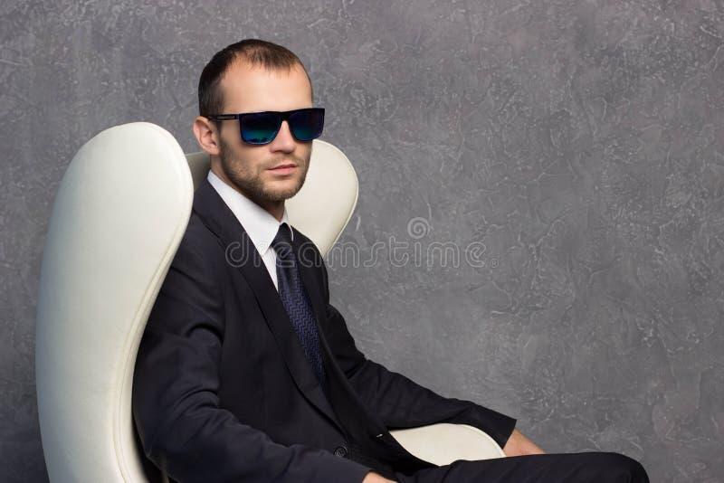 Homens de negócios 'sexy' brutais no terno com laço e óculos de sol que sentam-se na cadeira fotografia de stock
