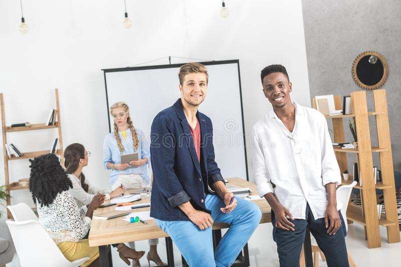 homens de negócios de sorriso multiculturais que olham a câmera e colegas que discutem o trabalho atrás fotos de stock royalty free