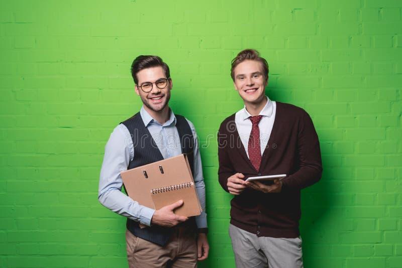 homens de negócios de sorriso novos com tabuleta digital e originais na frente de foto de stock royalty free