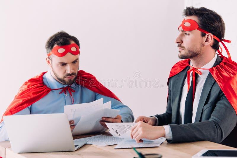 homens de negócios super consideráveis nas máscaras e cabos que trabalham com originais fotografia de stock royalty free