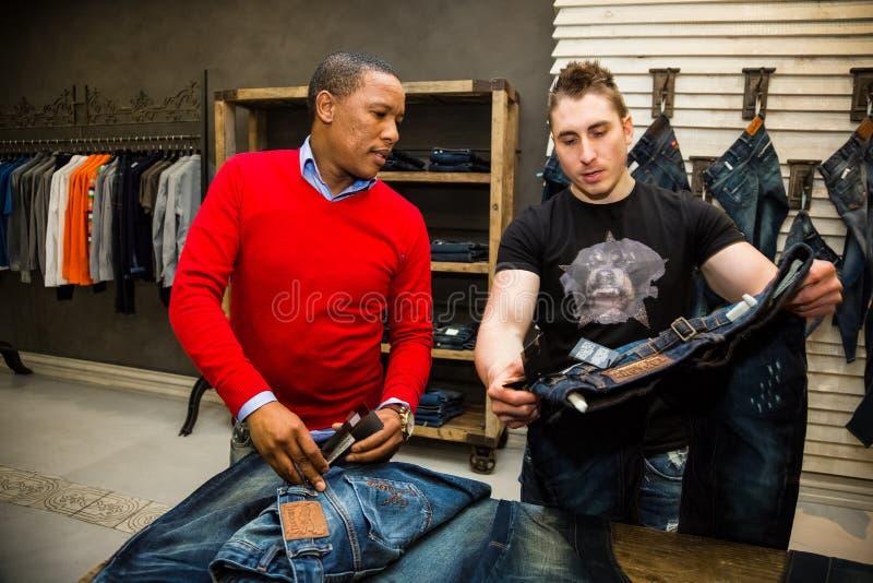 Homens diversos que compram calças de brim na alameda de luxo foto de stock royalty free