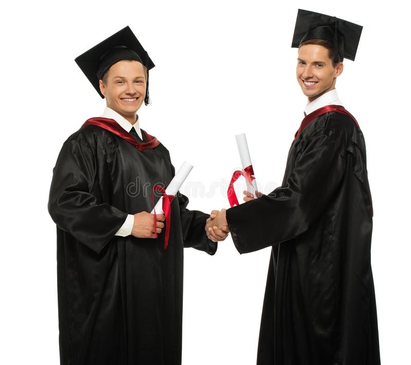 Homens do estudante graduado que agitam as mãos fotos de stock