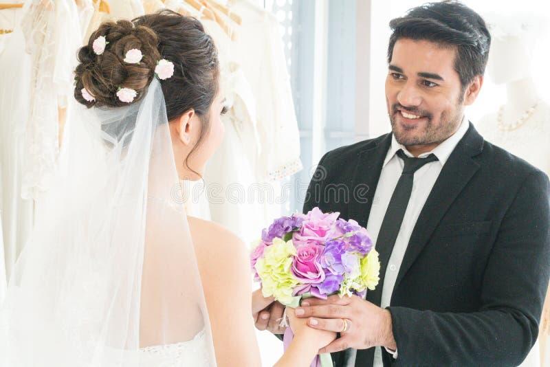 Homens do noivo que guardam as mãos de sua noiva com ramalhete fotos de stock royalty free
