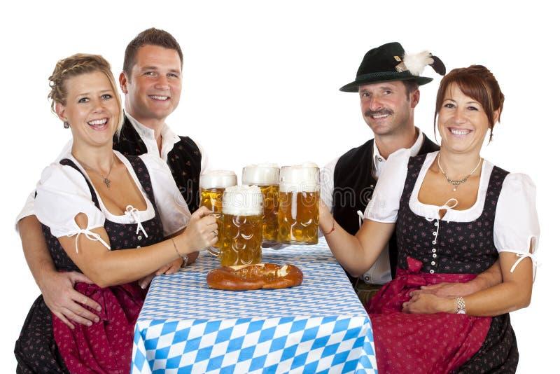 Homens e mulheres bávaros com o stein da cerveja de Oktoberfest imagem de stock royalty free