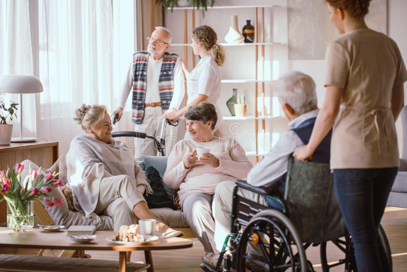 Homens e mulheres que falam na sala comum no lar de idosos imagem de stock