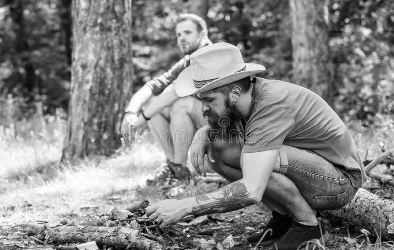 Homens em férias Conceito da masculinidade Guia final às fogueiras Como construir fora a fogueira Arranje os galhos das madeiras imagens de stock