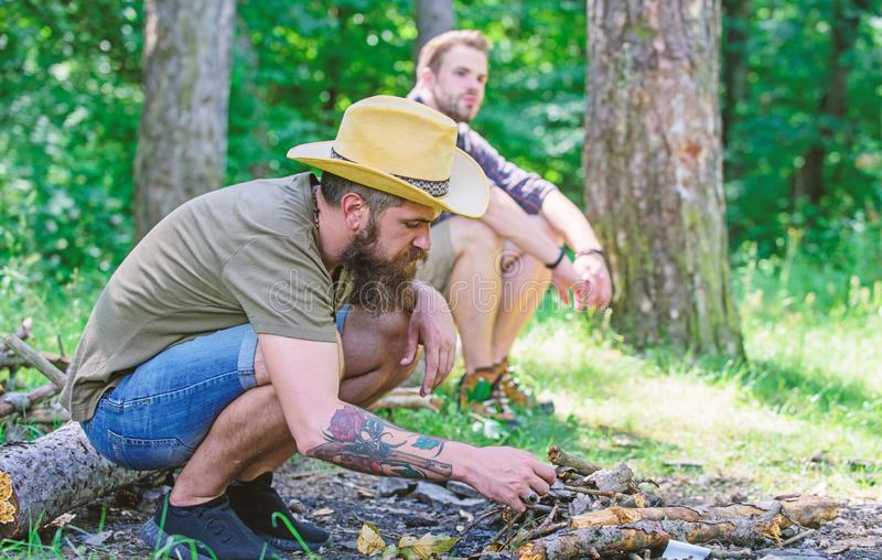 Homens em férias Conceito da masculinidade Guia final às fogueiras Como construir fora a fogueira Arranje os galhos das madeiras imagem de stock royalty free