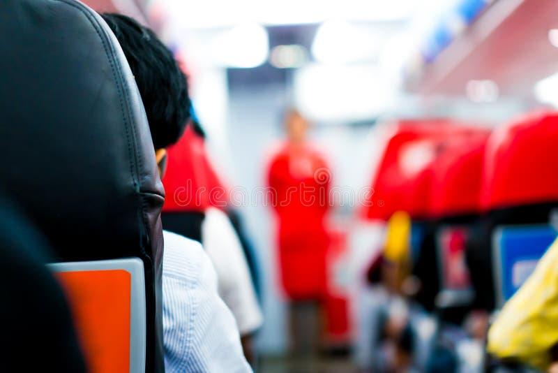 Homens em olhares do assento plano na aeromoça de bordo para explicar na parte dianteira da fileira fotos de stock royalty free
