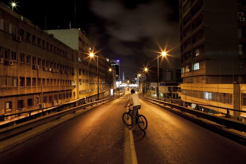 Homens em uma bicicleta na estrada escura fotos de stock royalty free