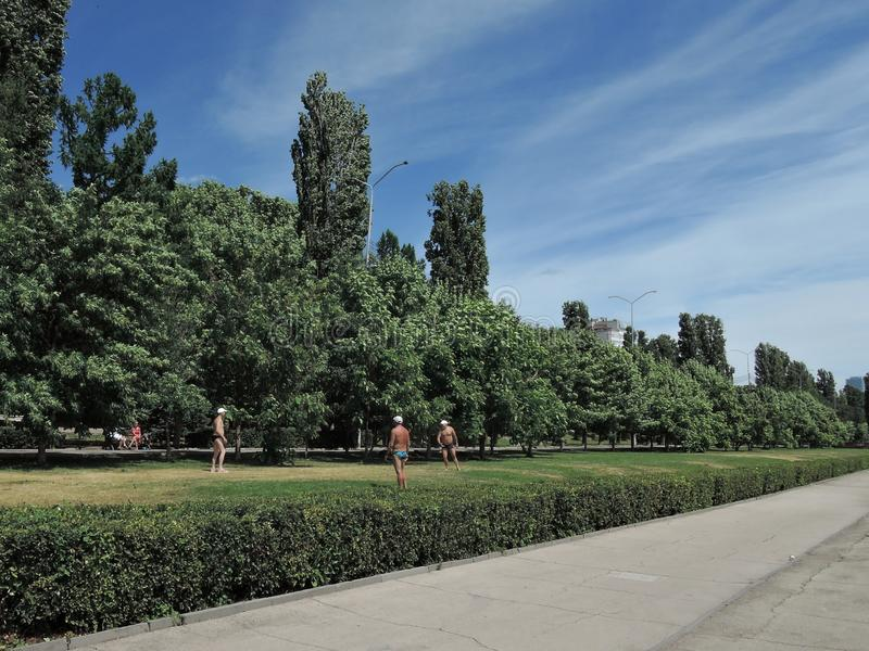 Homens idosos que jogam o Frisbee no gramado no parque em um dia quente Rússia, Saratov - em junho de 2019 imagens de stock