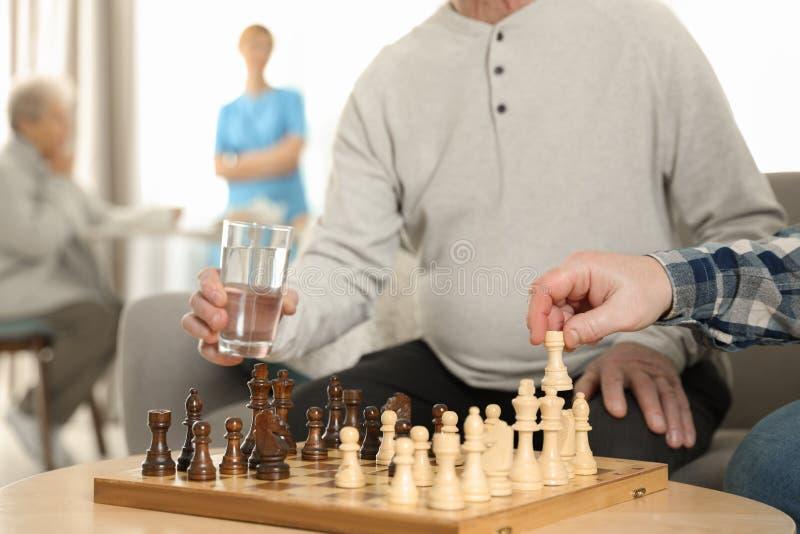 Homens idosos que jogam a xadrez no lar de idosos Ajudando a povos superiores imagens de stock royalty free