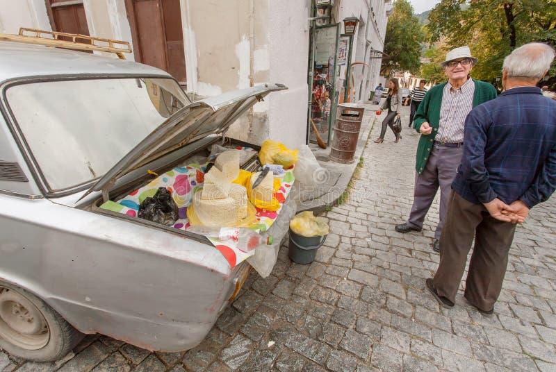 Homens idosos que vendem o queijo caseiro do contador no tronco do carro do vintage fotos de stock royalty free