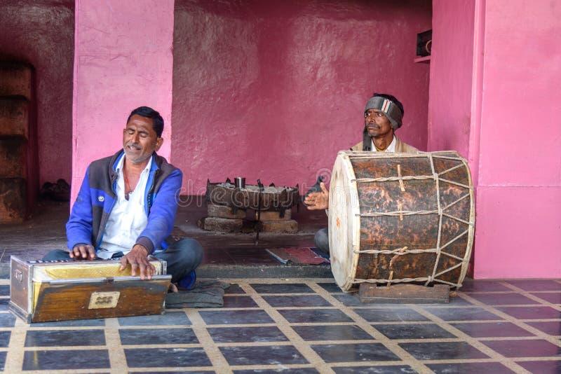 Homens indianos que jogam o cilindro e o harmônio em Karni Mata Temple ou templo dos ratos em Deshnok Rajasthan India imagens de stock