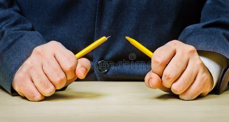 Homens irritados que quebram um lápis fotografia de stock