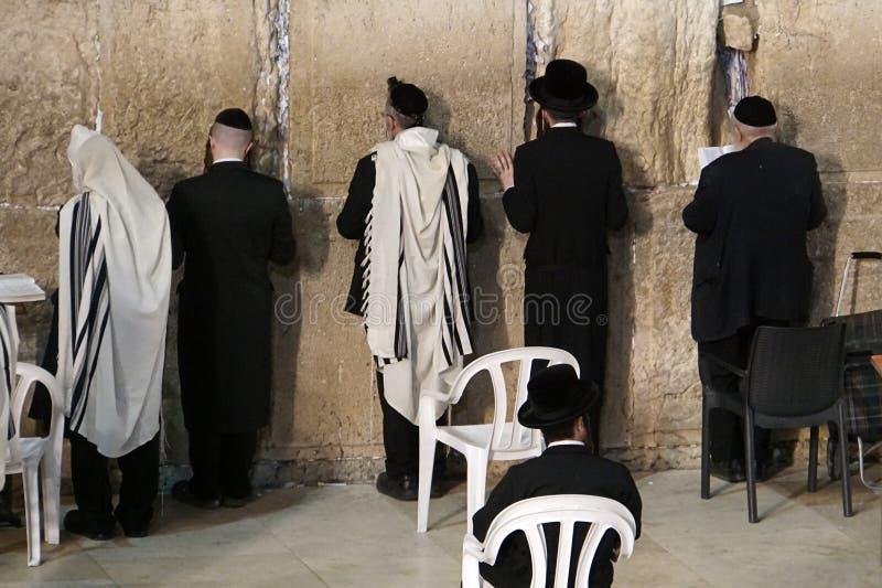 Homens judaicos de Othodox que lamentam na parede ocidental, parede lamentando, uma parede antiga da pedra calcária na cidade vel foto de stock royalty free
