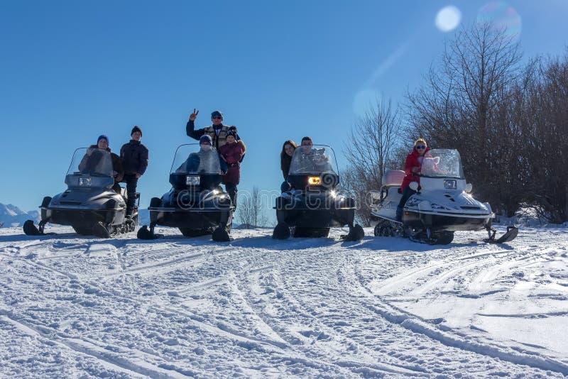 Homens, mulheres e crianças felizes novos nos carros de neve Yamaha em um dia ensolarado do inverno nevado da inclinação fotos de stock