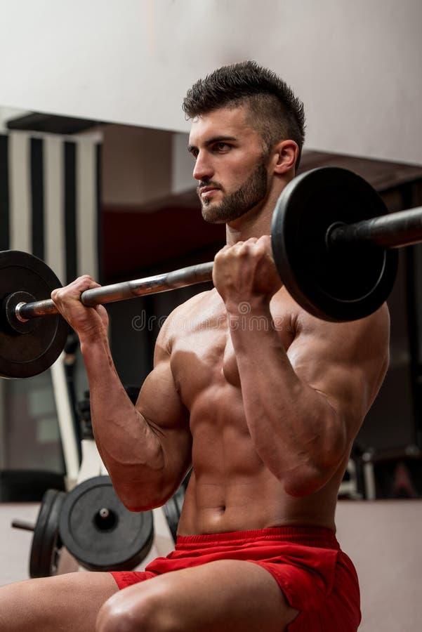 Homens musculares que fazem o exercício pesado para o bíceps imagem de stock