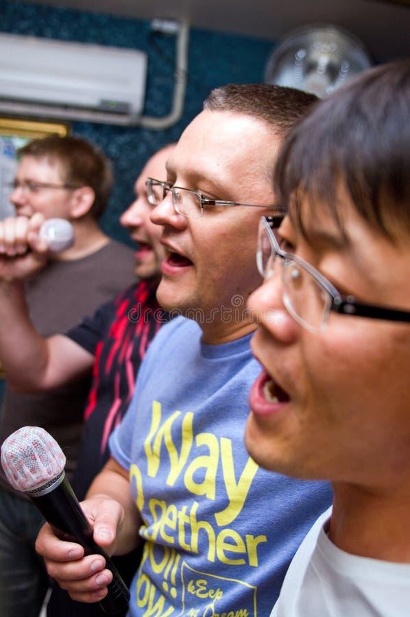 Homens no clube do karaoke fotografia de stock