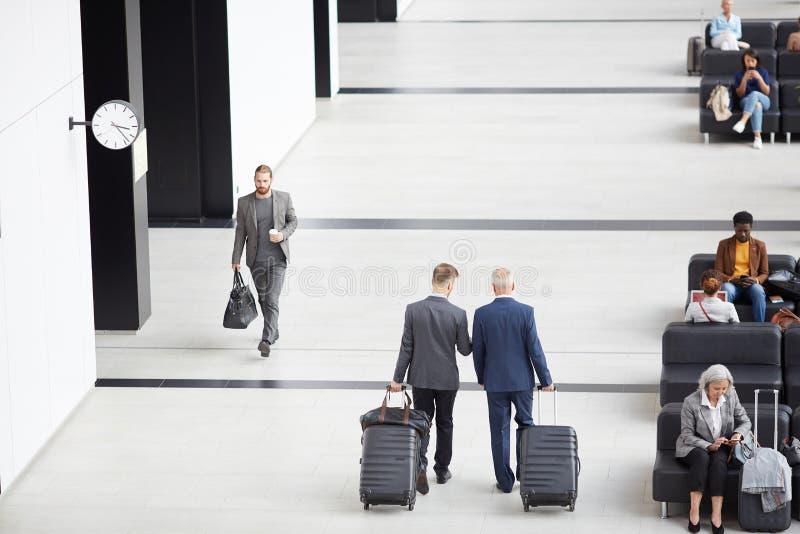 Homens nos ternos que movem-se ao longo do aeroporto fotografia de stock