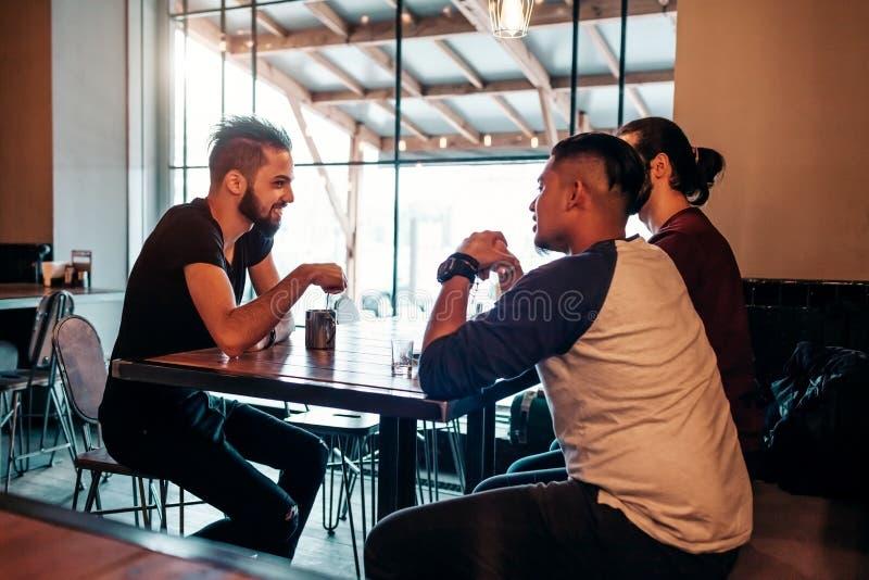 Homens novos árabes que penduram no café do sótão Os povos do Oriente Médio que falam na sala de estar barram e que têm bebidas imagem de stock royalty free