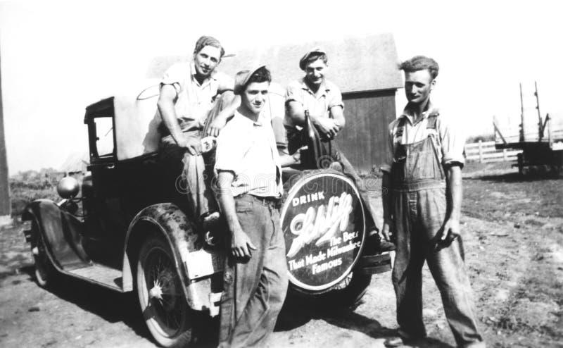 Homens novos da foto do vintage na exploração agrícola e no modelo T imagens de stock