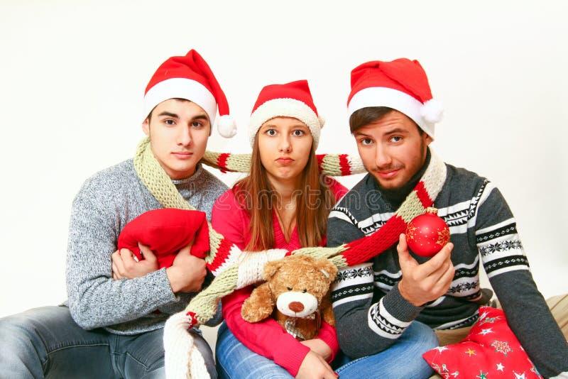 Homens novos e mulher com chapéus de Papai Noel imagem de stock