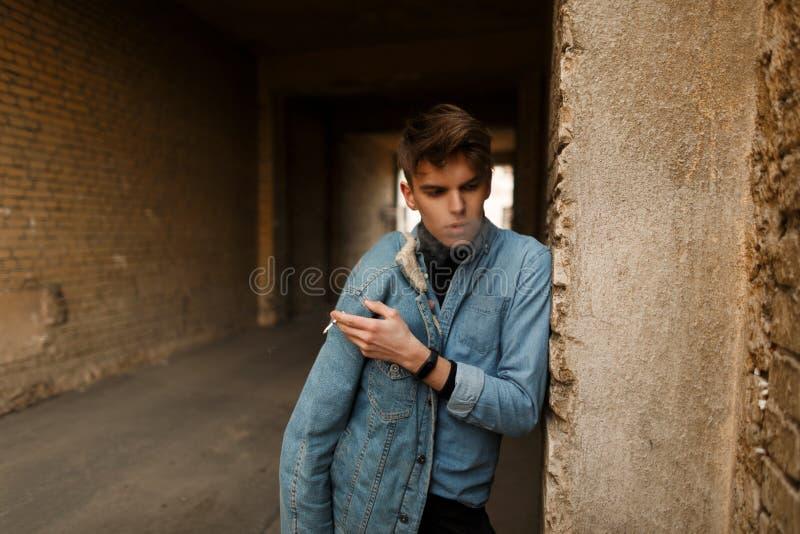 Homens novos elegantes em uma camisa da sarja de Nimes que fuma um cigarro fotografia de stock royalty free