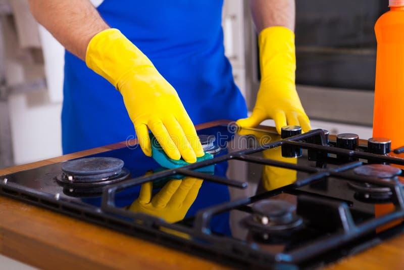 Homens novos na limpeza protetora de borracha e no fogão do polimento preto imagem de stock