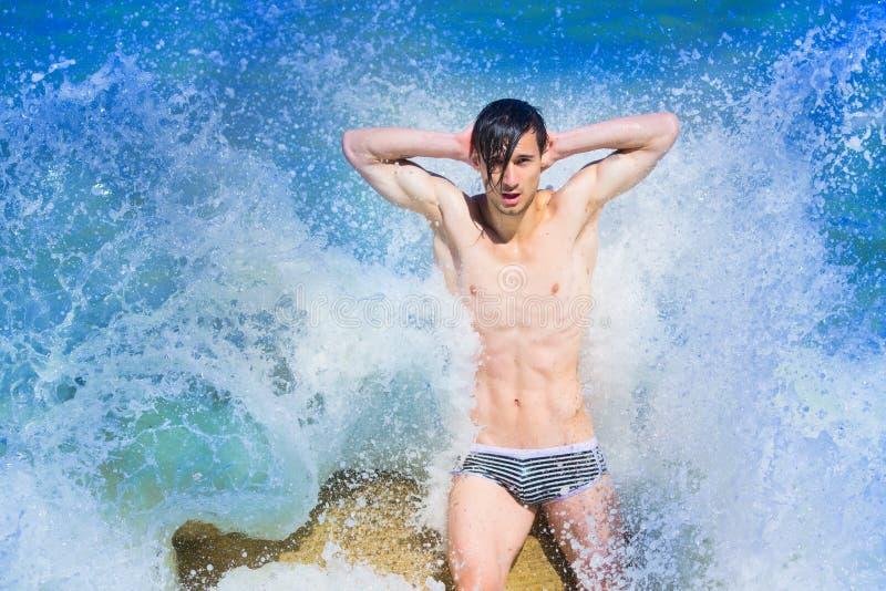 Homens novos na praia imagem de stock