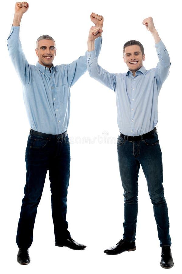 Homens novos ocasionais que ganham e que comemoram fotos de stock