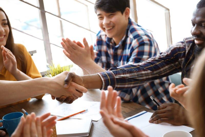 Homens novos que agitam as mãos na tabela no escritório Conceito da unidade imagem de stock