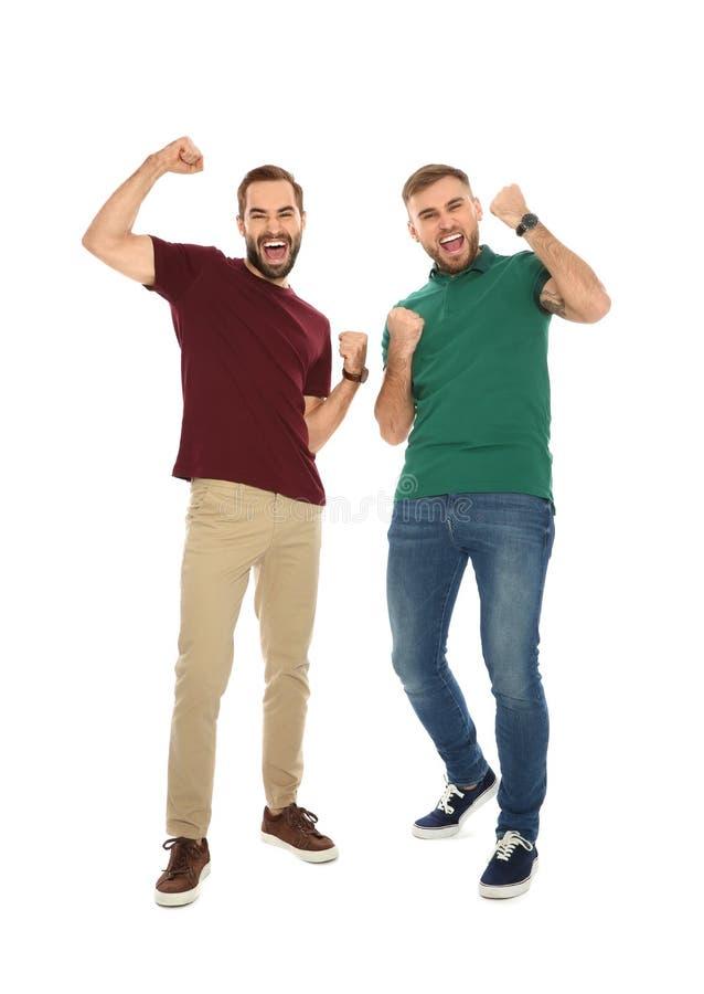 Homens novos que comemoram a vitória foto de stock