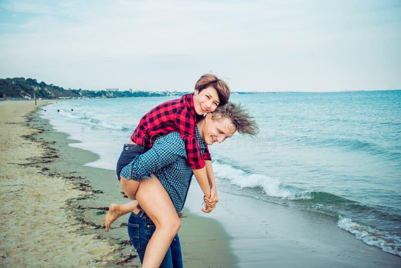 Homens novos que dão às cavalitas o passeio às mulheres na praia Pares novos que têm o divertimento junto com o fundo azul do oce imagem de stock