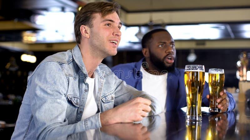 Homens novos que enra?zam a equipe de esporte favorita, bar em linha de observa??o da competi??o, lazer foto de stock