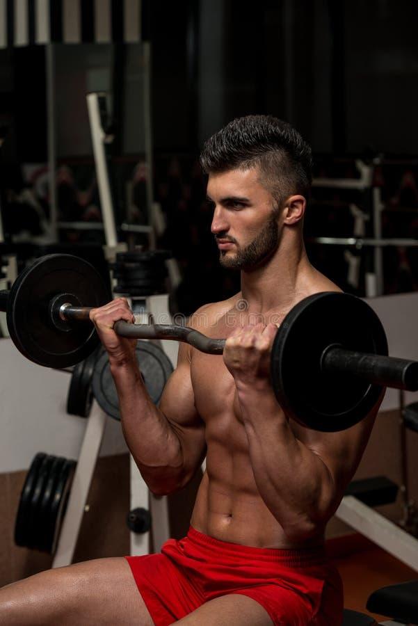 Homens novos que fazem o exercício para o bíceps foto de stock royalty free