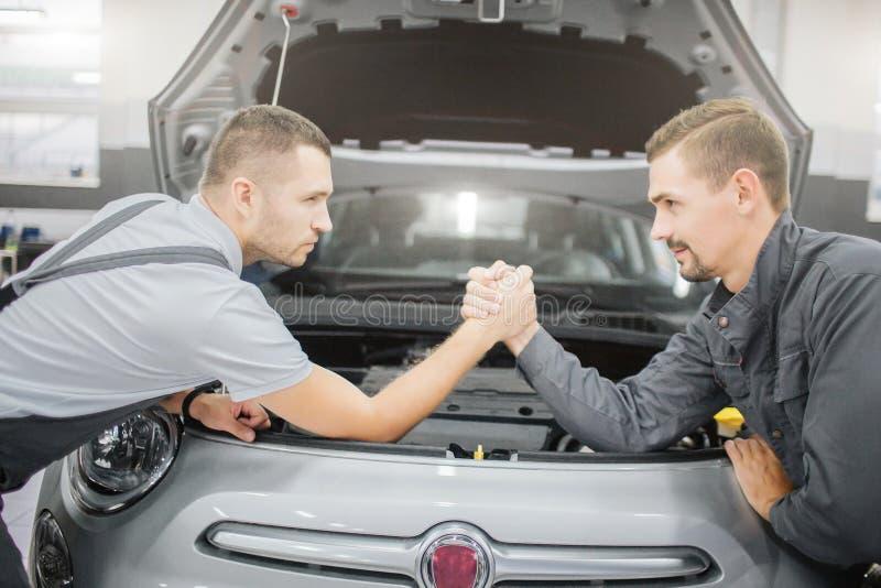 Homens novos que fazem um acordo entre se Inclinam-se ao carro e guardam-se as mãos de cada um A parte dianteira do corpo de carr fotografia de stock