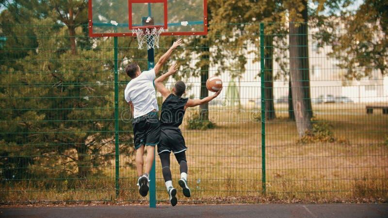 Homens novos que jogam o basquetebol no ar livre da terra de esportes - protegendo a aro de basquetebol do ataque imagens de stock