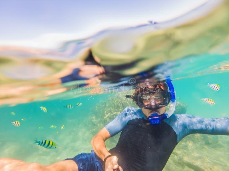 Homens novos que mergulham o fundo subaquático de exploração da paisagem do recife de corais no oceano azul profundo com peixes c foto de stock