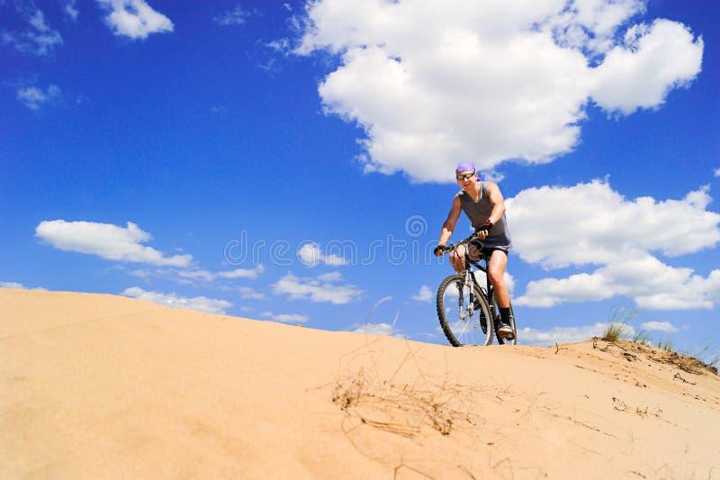 Homens novos que montam uma bicicleta fotografia de stock royalty free