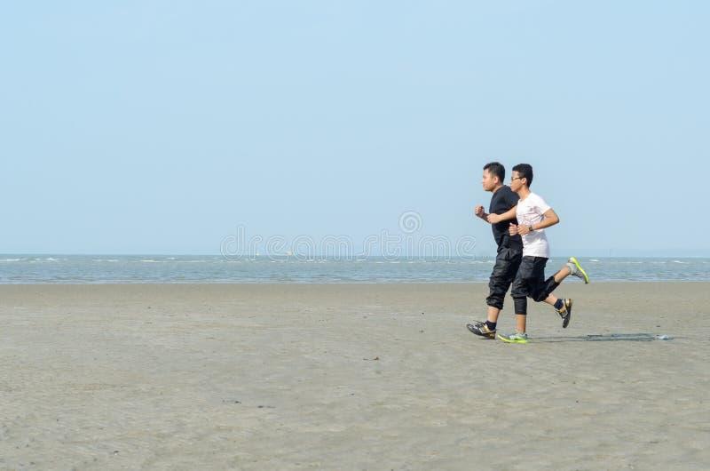 Homens novos que movimentam-se na praia fotografia de stock royalty free