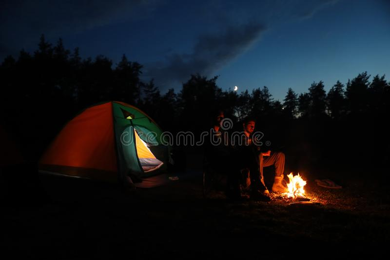 Homens novos que sentam-se perto da fogueira e da barraca de acampamento na região selvagem imagem de stock royalty free